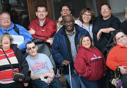 A group of men and women with disabilities stand outside.