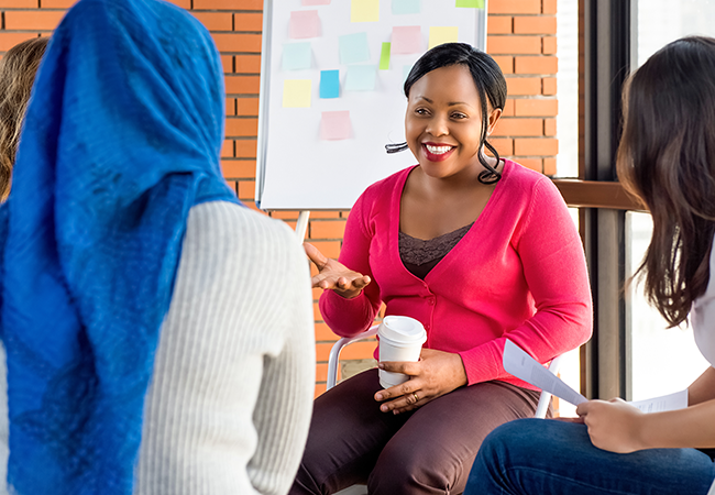 A young African-American woman sits among two other women, one wearing a hijab, and leads a meeting in front of a whiteboard.